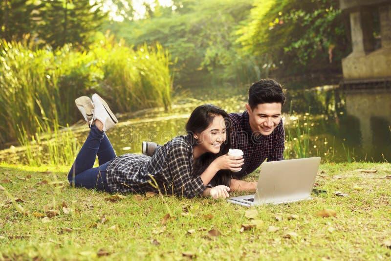 Atrakcyjni azjatykci pary dopatrywania filmy na laptopie podczas gdy kłamający dalej zdjęcia stock