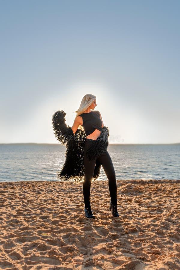 Atrakcyjni blondyny modelują w czerni ubraniach pozuje w promieniach powstający słońce przy nadmorski obraz royalty free