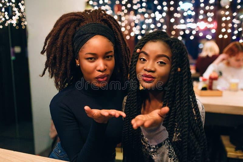 Atrakcyjni i piękni afrykańscy modele patrzeją prostymi i wysyłają buziaki One uśmiechają się wpólnie i siedzą Młodych kobiet spo obraz royalty free
