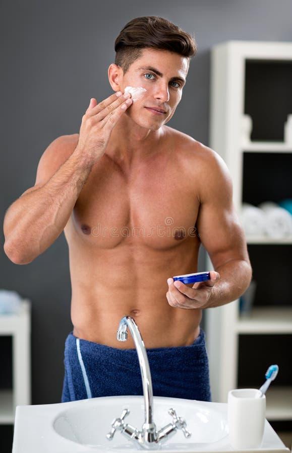 Atrakcyjni męscy kładzenie kosmetyki kremowi na twarzy zdjęcia stock