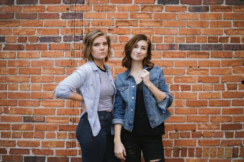 Atrakcyjni Młodzi Żeńscy najlepsi przyjaciele Modeluje zabawę przed Ceglaną Miastową ścianą i Ma zdjęcia royalty free