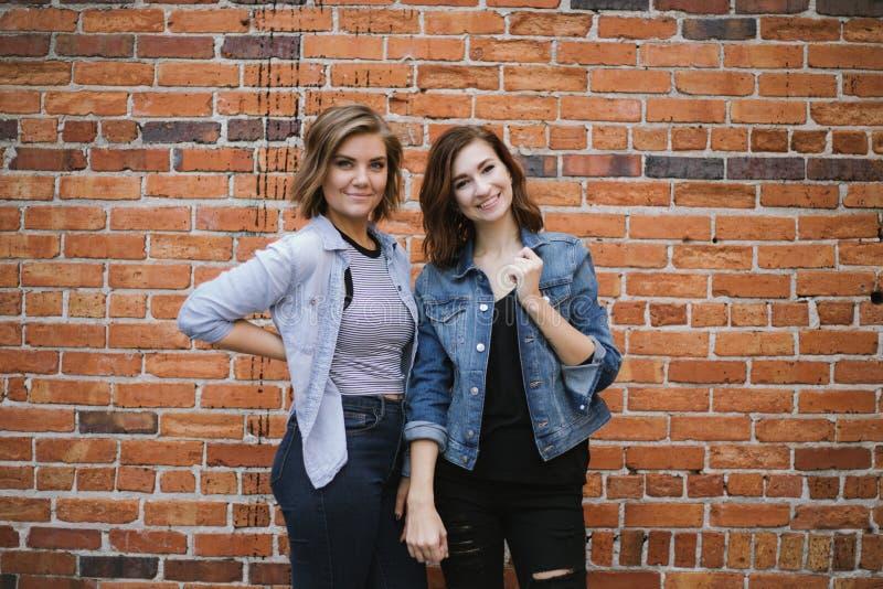 Atrakcyjni Młodzi Żeńscy najlepsi przyjaciele Modeluje zabawę przed Ceglaną Miastową ścianą i Ma obrazy stock