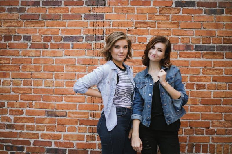 Atrakcyjni Młodzi Żeńscy najlepsi przyjaciele Modeluje zabawę przed Ceglaną Miastową ścianą i Ma zdjęcia stock