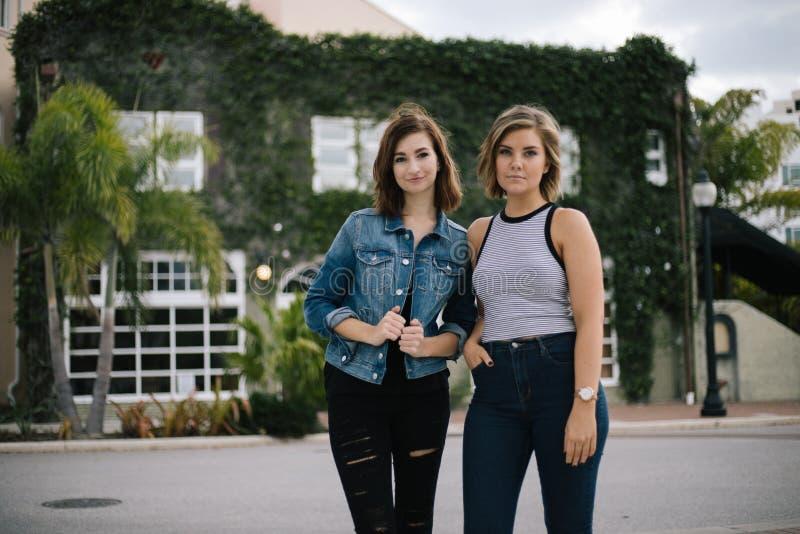 Atrakcyjni Młodzi Żeńscy najlepsi przyjaciele Modeluje zabawę przed Porosłym Miastowym budynkiem i Ma obraz stock
