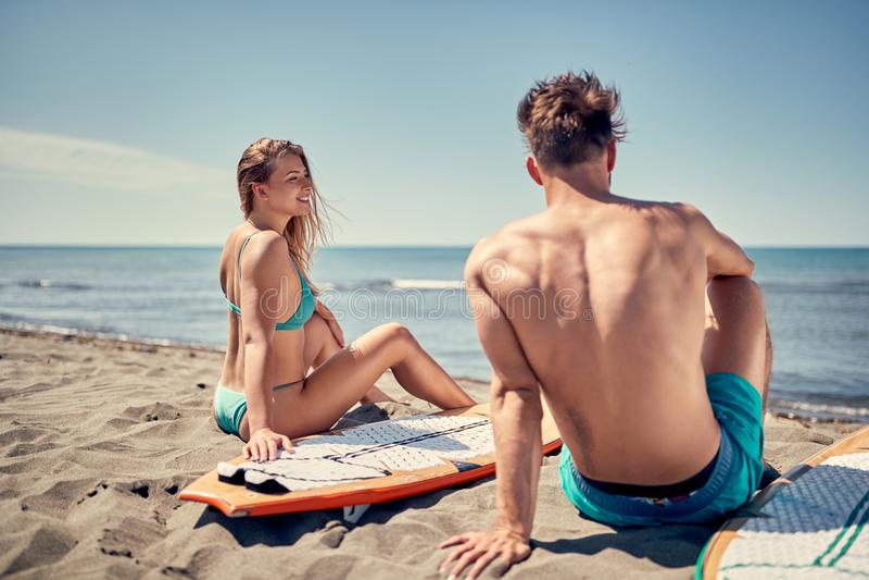 Atrakcyjni pary outdoors - surfingowowie na plażowych Wodnych sportach zdjęcia stock