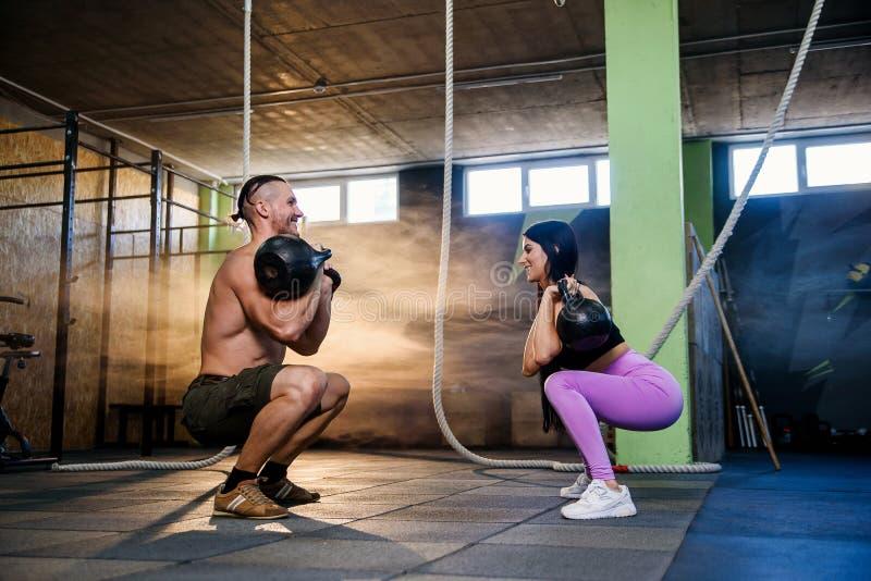 Atrakcyjni potomstwa dobierają się w sport odzieży robi ćwiczeniu w gym obraz royalty free