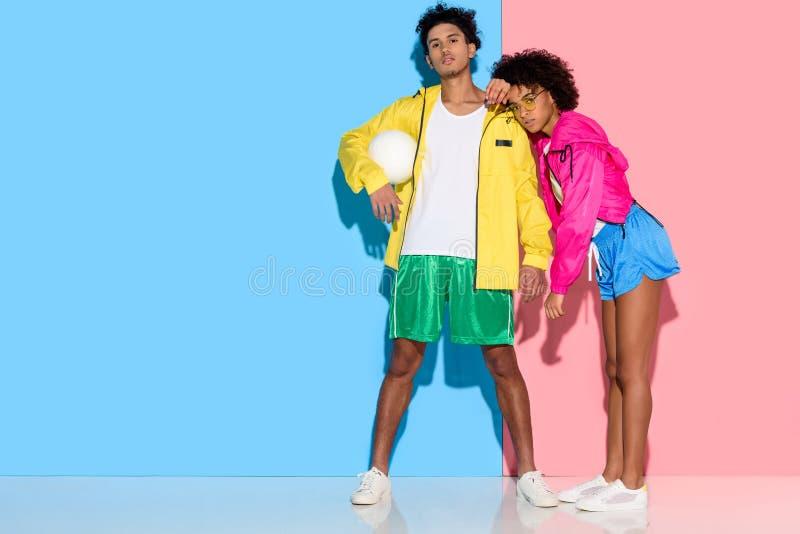 Atrakcyjni potomstwa dobierają się w sportswear pozyci przeciw menchiom i błękitowi obraz stock