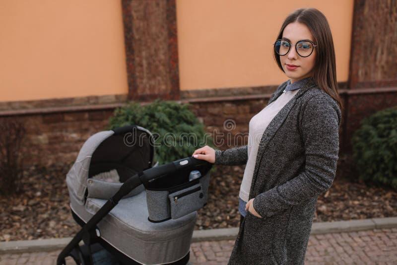 Atrakcyjni potomstwa matkują odprowadzenie z jej małym dzieckiem Mama z nowonarodzonym dzieckiem w pram zdjęcia royalty free