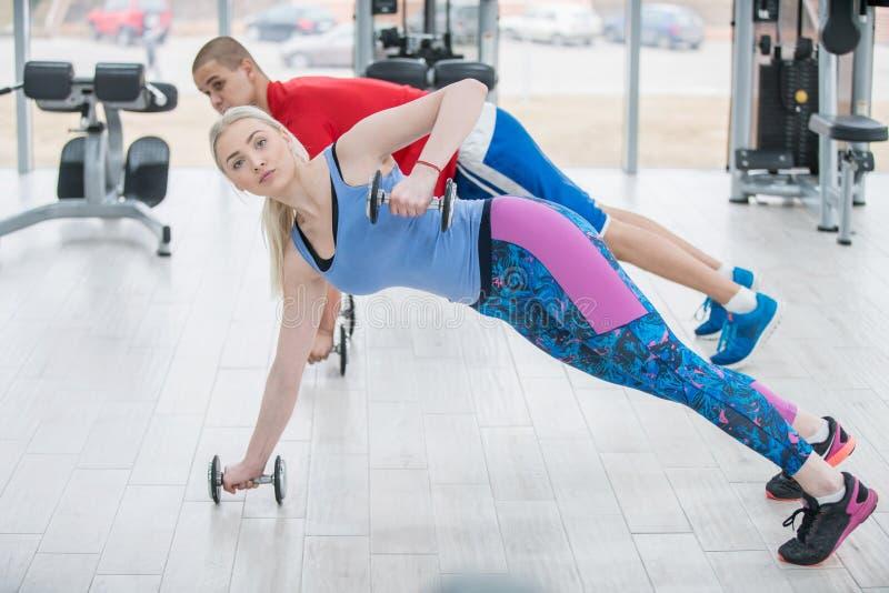 Atrakcyjni sportów ludzie są pracujący z dumbbells w gym out zdjęcie royalty free