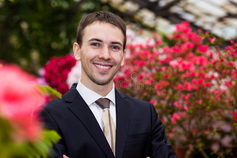 Atrakcyjni uśmiechnięci młodzi człowiecy w garniturze w kwiatu ogródzie zdjęcia stock