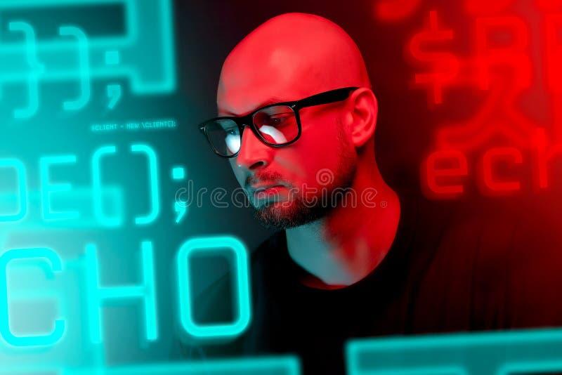 Atrakcyjny łysy mężczyzna z brodą w szkłach na neonowego światła tle obrazy royalty free