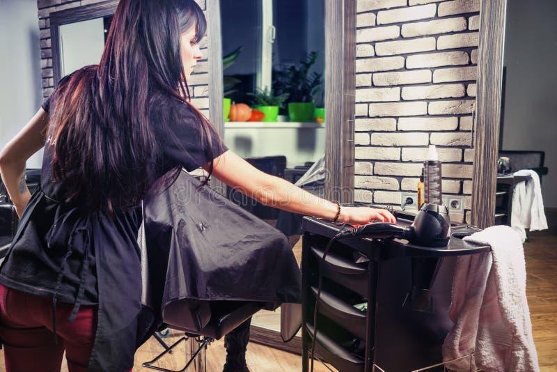 Atrakcyjny żeński fryzjer bierze niektóre fachowych hairdress zdjęcia royalty free