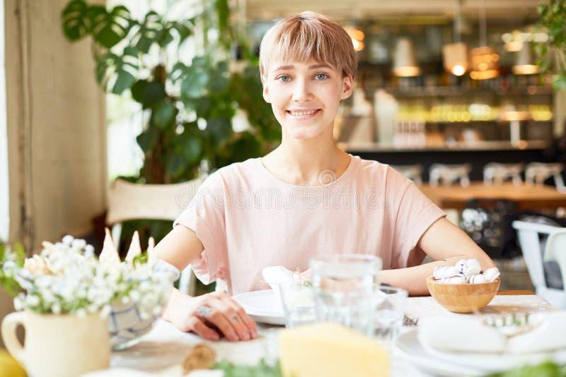 Atrakcyjny żeński obsiadanie w cukiernianym i uśmiechniętym fotografia stock