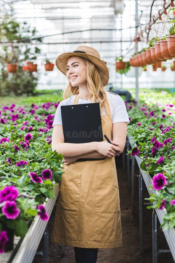 Atrakcyjny żeński ogrodniczki mienia schowek kwiatami fotografia stock