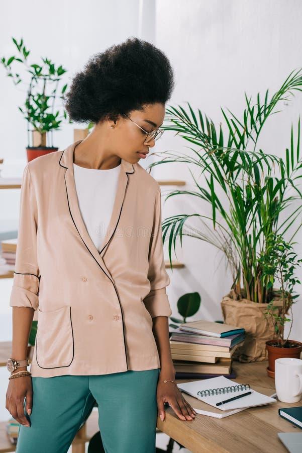 atrakcyjny amerykanin afrykańskiego pochodzenia bizneswoman stoi blisko stołu w biurowym i przyglądającym fotografia stock