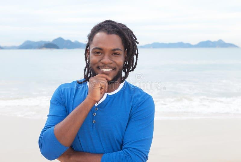 Atrakcyjny amerykanina afrykańskiego pochodzenia facet z dreadlocks przy plażą zdjęcie stock