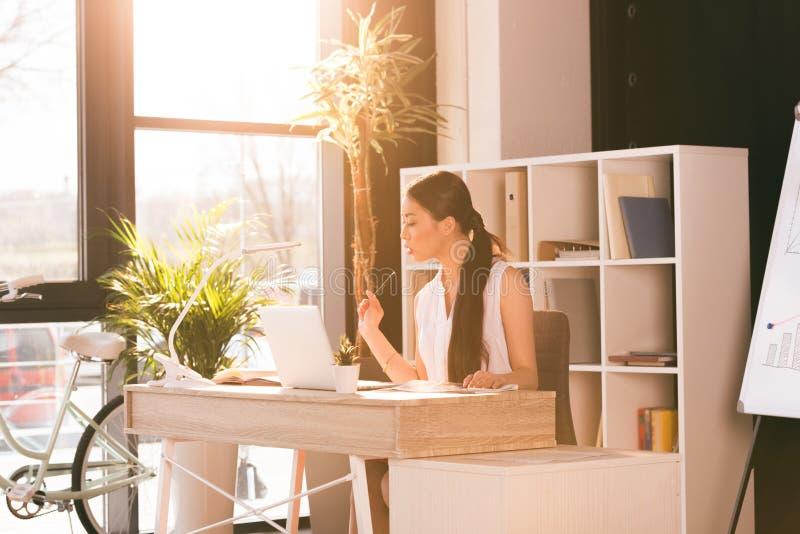 Atrakcyjny azjatykci bizneswoman pracuje z laptopem przy miejscem pracy w biurze obrazy royalty free