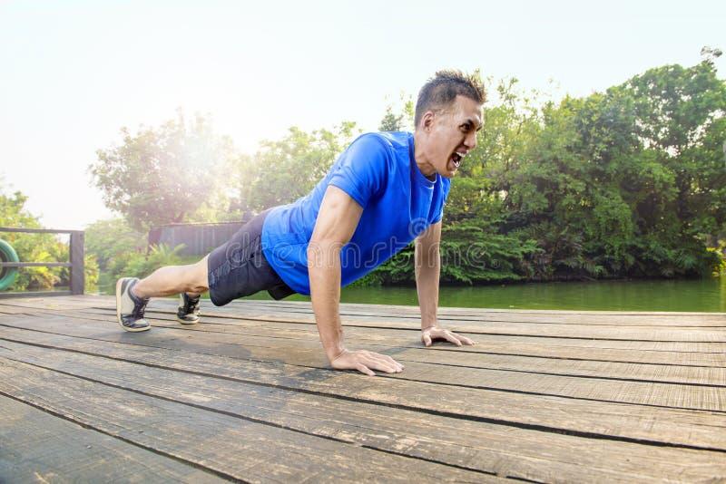 Atrakcyjny azjatykci mężczyzna robić pcha up ćwiczenie zdjęcie royalty free