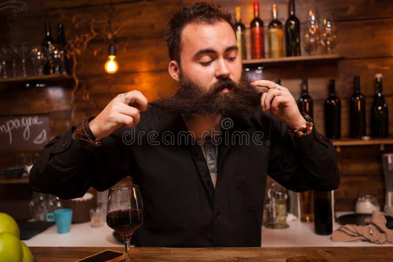 Atrakcyjny barman bawi? si? z jego d?ugo brod? za kontuarem zdjęcia royalty free