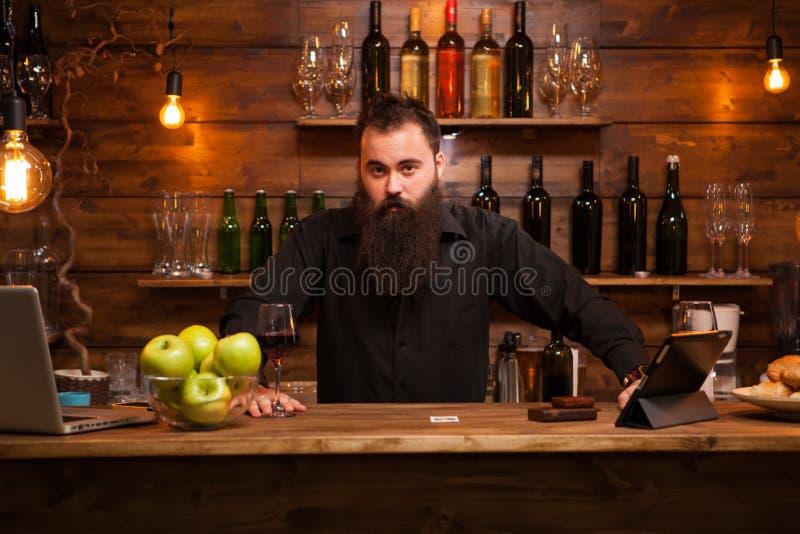 Atrakcyjny barman bawi? si? z jego d?ugo brod? za kontuarem obraz royalty free