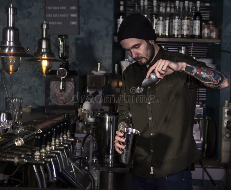 Atrakcyjny barman robi koktajlowi zdjęcia royalty free