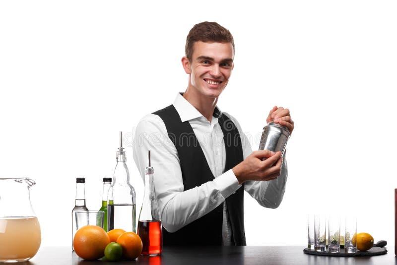 Atrakcyjny barman z potrząsaczem przy prętowym kontuarem, wapno, pomarańcze, cytryny na białym tle fotografia royalty free