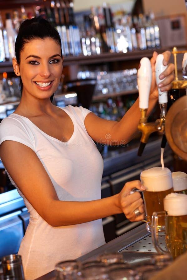 Atrakcyjny barmanu klapania piwo w barze fotografia stock