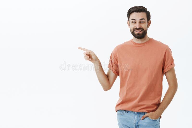 Atrakcyjny beztroski, życzliwy męski przyjaciel niezobowiązująco wskazuje w przypadkowej koszulce i patrzejący kamerę obrazy stock