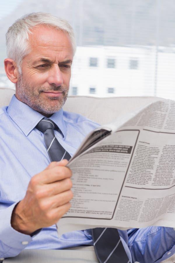 Atrakcyjny biznesmen czyta gazetę na leżance fotografia royalty free