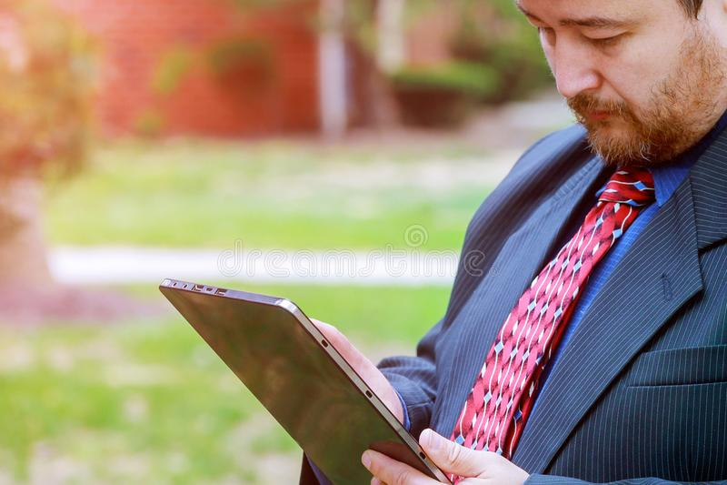 Atrakcyjny biznesmen trzyma cyfrową pastylkę outdoors pracuje w zewnętrznych budynkach biurowych w kostiumu i krawacie zdjęcie royalty free