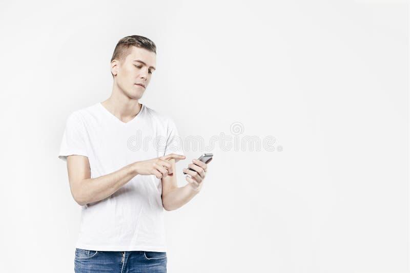 Atrakcyjny biznesowego mężczyzna model w białej koszulce odizolowywającej na biały dzwonić telefonem komórkowym, pchnięcie guzikó zdjęcia stock