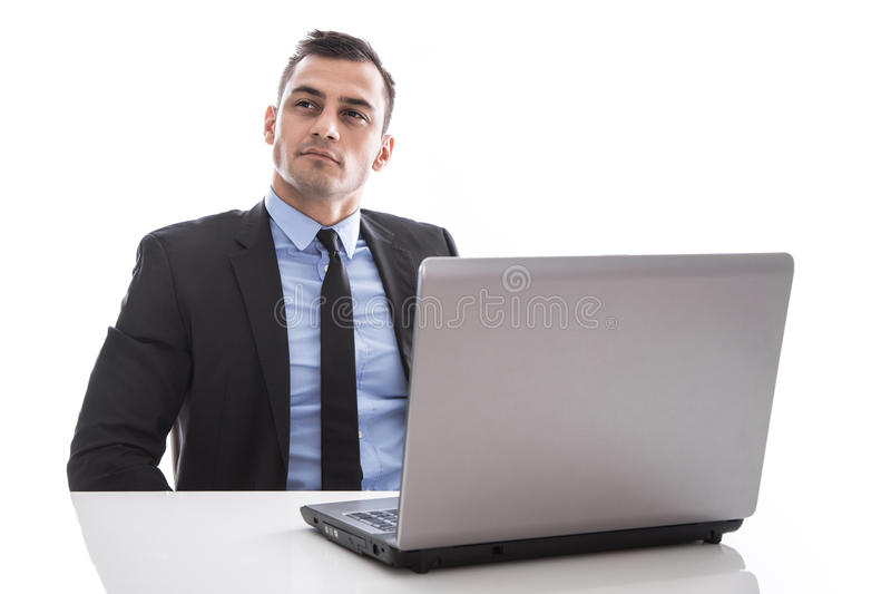 Atrakcyjny biznesowego mężczyzna obsiadanie przy biurkiem z laptopem myśleć iso obraz stock