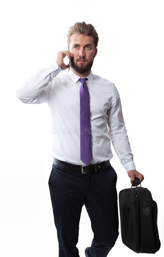 Atrakcyjny biznesowy mężczyzna z brodą jest chodzący i opowiadający na mądrze telefonie zdjęcia royalty free