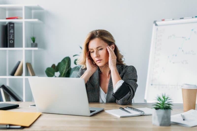 atrakcyjny bizneswoman ma migrenę i patrzeje laptop zdjęcie stock