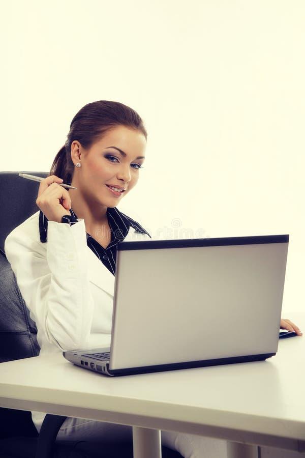 Atrakcyjny bizneswoman pracuje z laptopem przy biurem obraz stock