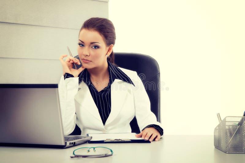Atrakcyjny bizneswoman pracuje z laptopem przy biurem obrazy stock