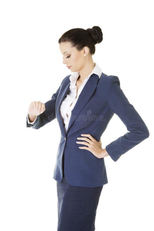 Atrakcyjny bizneswoman sprawdza czas zdjęcie stock