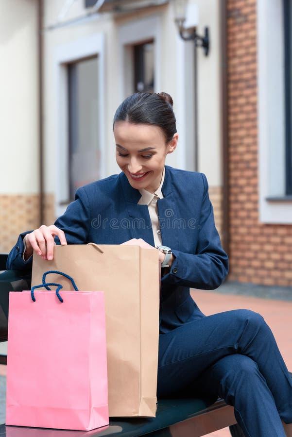 atrakcyjny bizneswomanu obsiadanie na ławce i patrzeć w zdjęcia royalty free