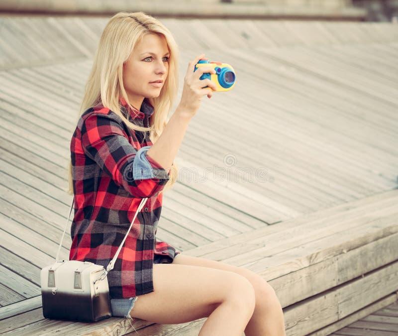 Atrakcyjny blond kobiety obsiadanie na drewnianej podłoga i fotografujący z zabawkarską kamerą zdjęcia royalty free