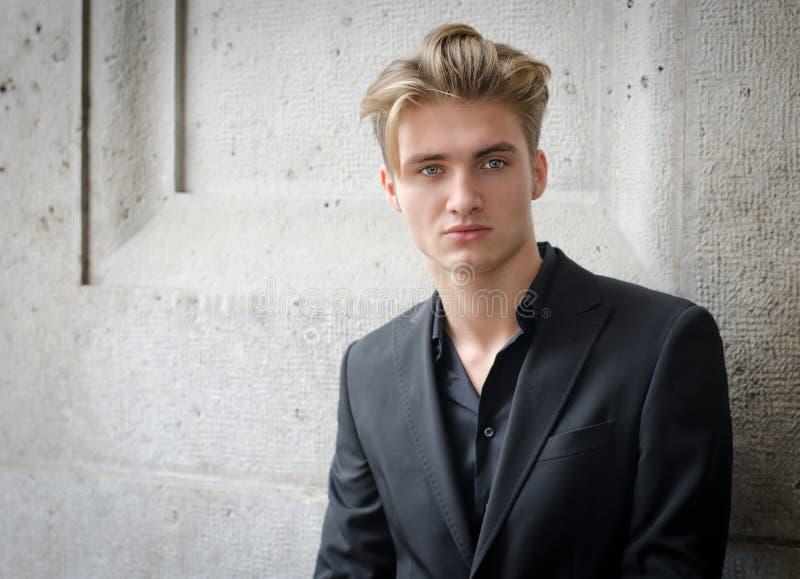 Atrakcyjny blond młody człowiek w kurtce, przeciw ścianie obraz stock