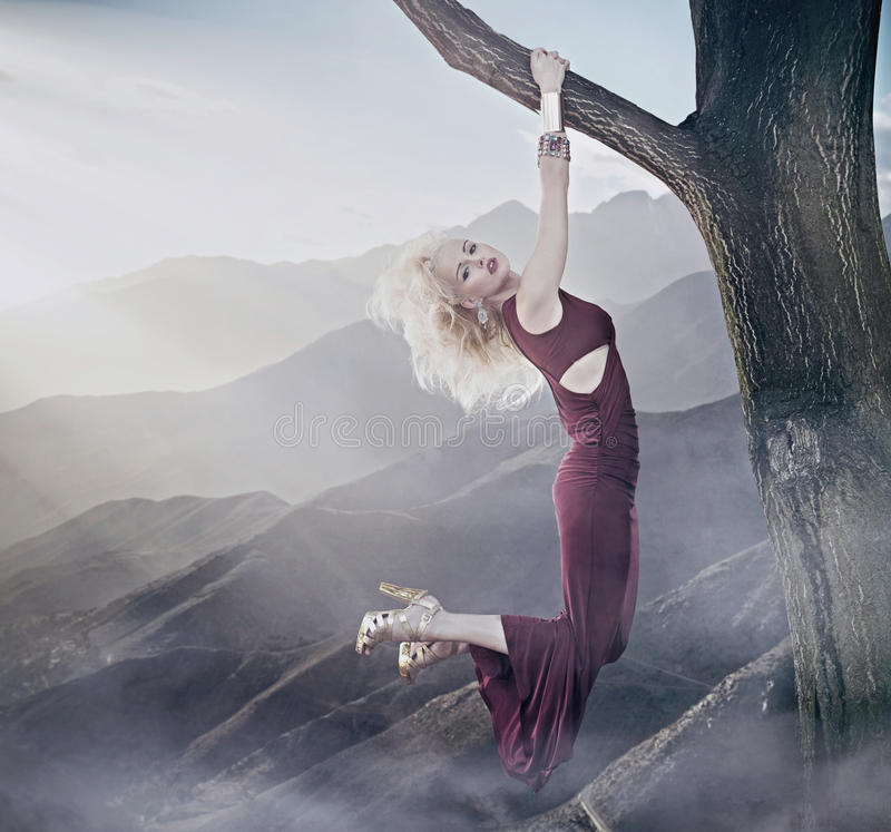 Atrakcyjny blondynki damy obwieszenie na drzewie obraz royalty free