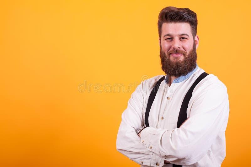 Atrakcyjny brodaty mężczyzna w białej uśmiechniętej i przyglądającej athe kamerze nad żółtym tłem zdjęcie royalty free