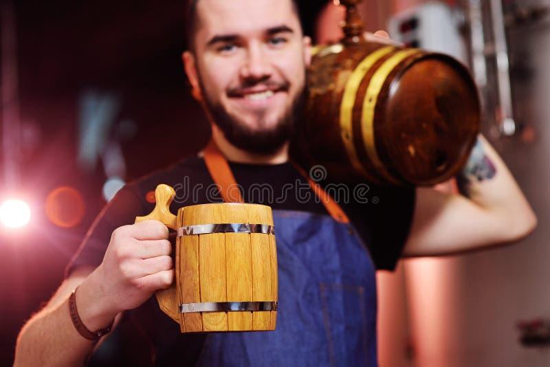 Atrakcyjny brodaty piwowar z drewnianym kubkiem w jego z baryłką ono uśmiecha się przy tłem piwo i ręki zdjęcie stock