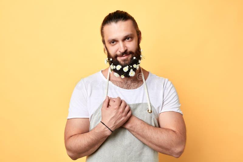 Atrakcyjny, brutalny brodaty rozochocony mężczyzna z kwiatami w brodzie, obraz royalty free