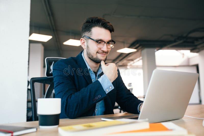 Atrakcyjny ciemnowłosy mężczyzna pracuje z laptopem przy stołem w biurze Jest ubranym błękitną koszula z czarną kurtką Jest fotografia stock
