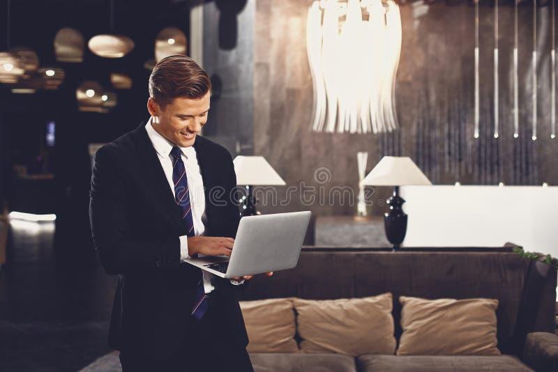 Atrakcyjny czÅ'owiek stojÄ…cy w holu i trzymajÄ…cy laptopa zdjęcie royalty free