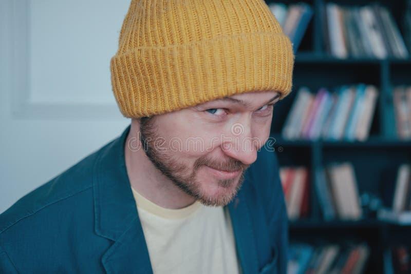 Atrakcyjny dorosły brodaty mężczyzny modniś w żółtych kapeluszy spojrzeniach w kamerę slyly i uśmiechy na błękit ściany tle obrazy stock