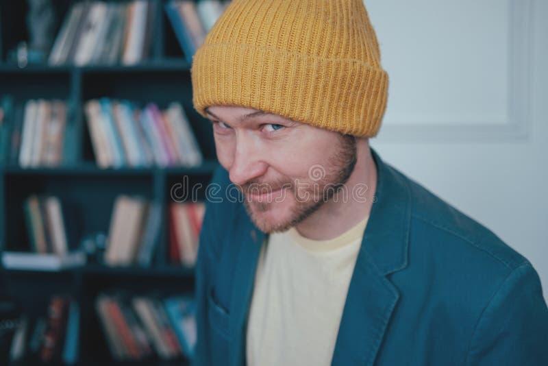 Atrakcyjny dorosły brodaty mężczyzny modniś w żółtych kapeluszy spojrzeniach w kamerę slyly i uśmiechy na błękit ściany tle obraz royalty free