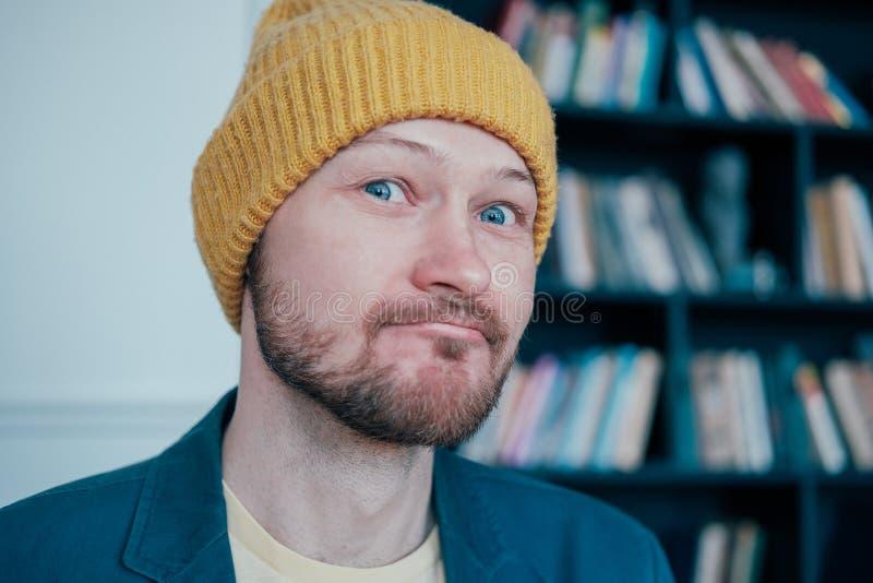 Atrakcyjny dorosły brodaty mężczyzny modniś w żółtych kapeluszy spojrzeniach w kamerę slyly i uśmiechy na błękit ściany tle fotografia stock