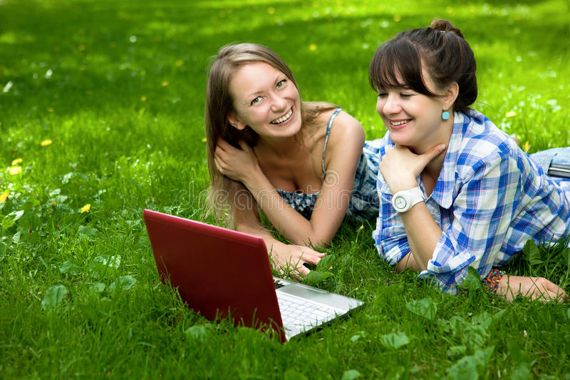 atrakcyjny dziewczyn laptopu park dwa zdjęcie stock